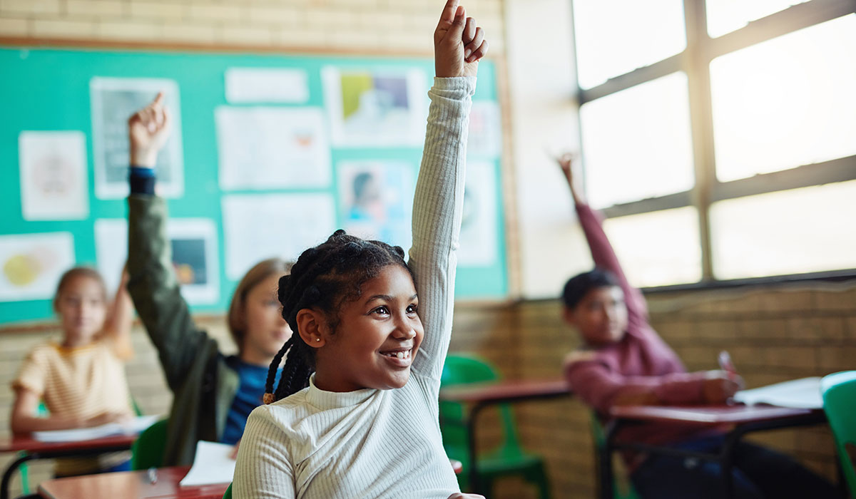 Young girl raising hand in classroom.