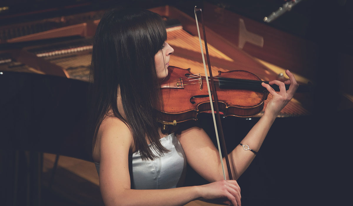 Young female concert violinist performing on stage.