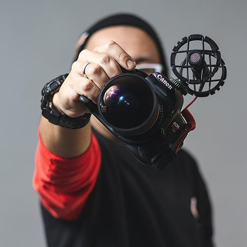 man holding Canon camera in front of face